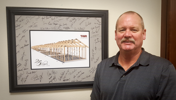 Cary Skeen standing in front of a signed photo